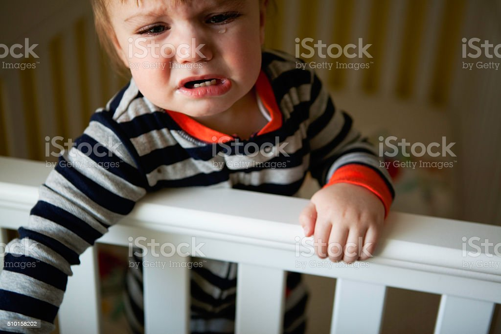 Baby Boy Crying in Crib stock photo