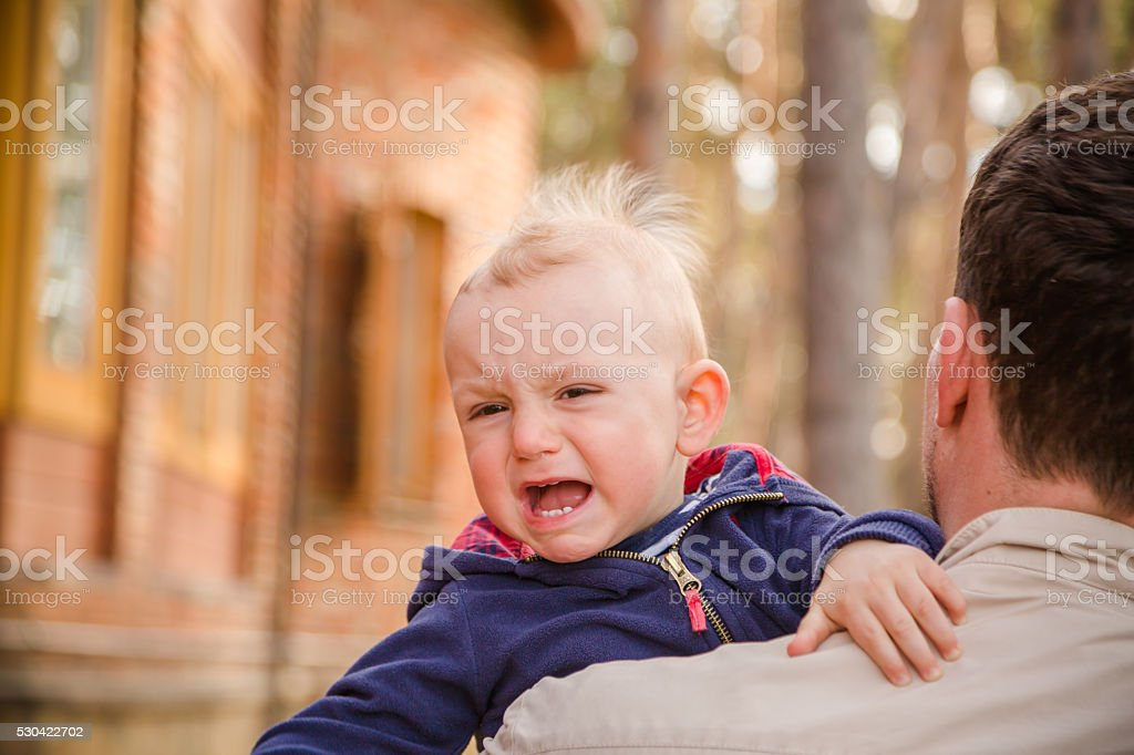 Baby boy crying on his father shoulder stock photo