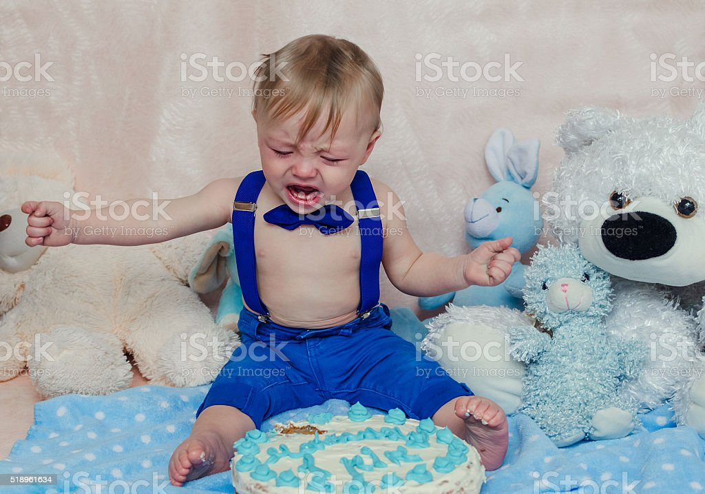 Baby boy crying while eating his birthday party cake stock photo