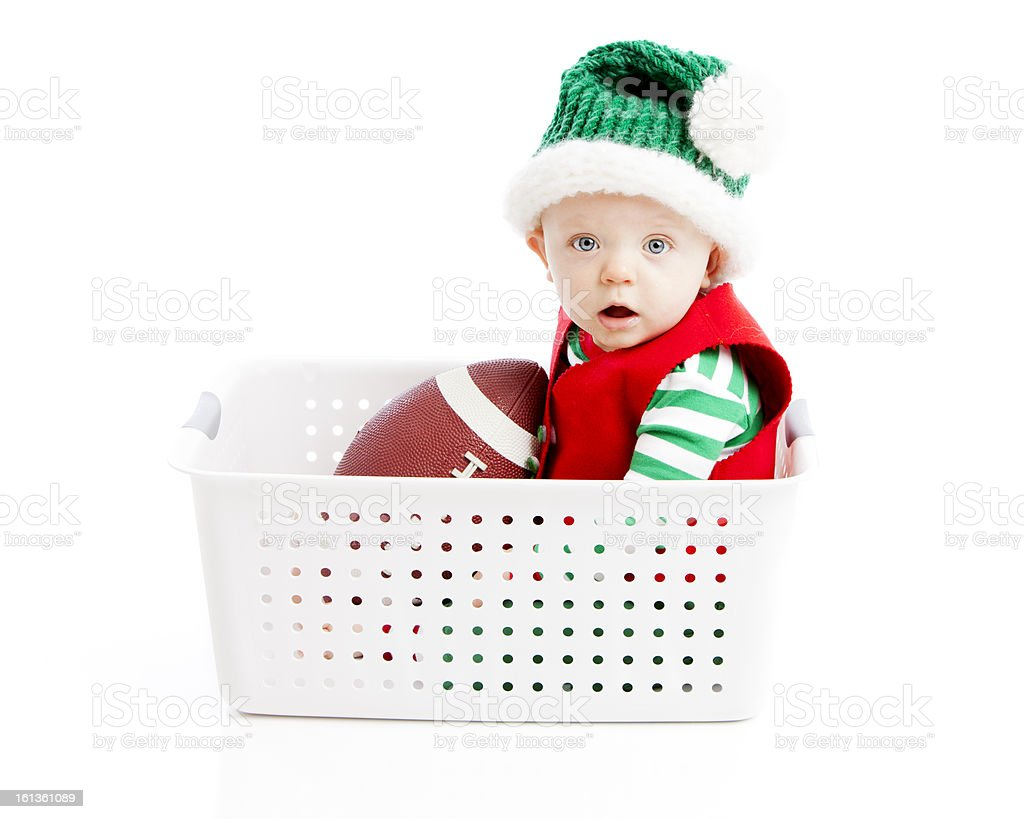 Baby Boy Dressed as Elf Rides Pretend Sleigh with Football stock photo