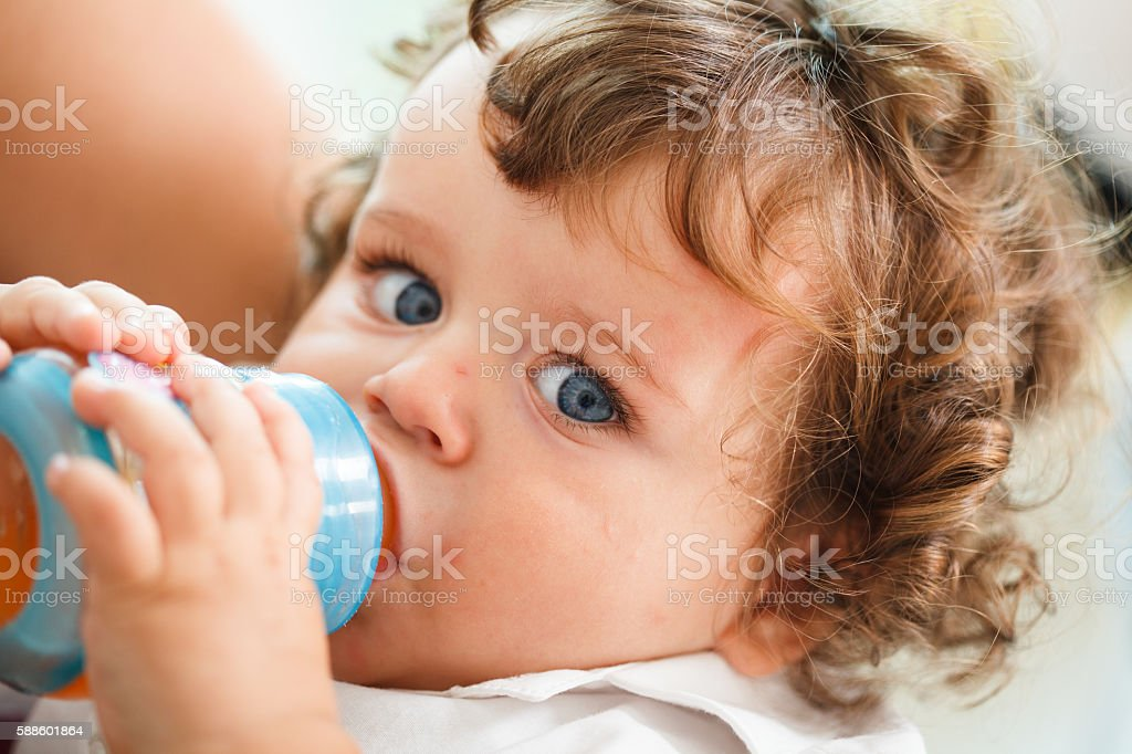 Baby boy (6-12 months) drinking from bottle stock photo
