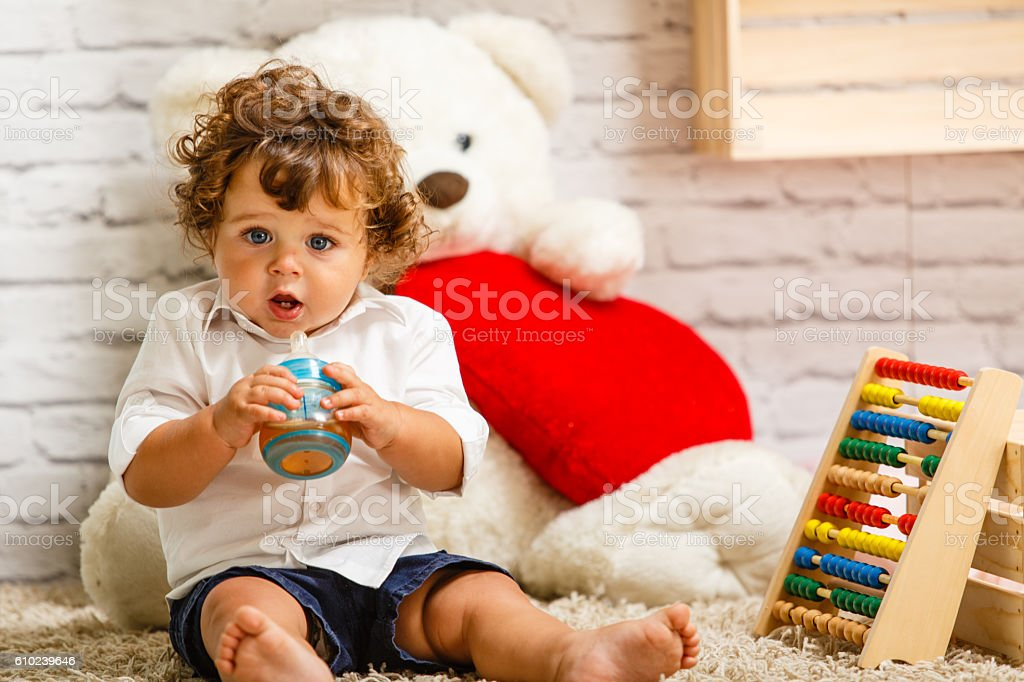 Baby boy drinking juice from a bottle stock photo