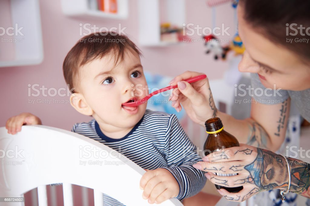 Baby boy drinking medicine off a spoon stock photo