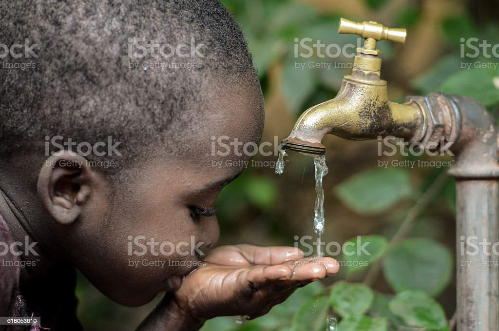 Baby Boy Drinks Water from Tap in a Garden stock photo