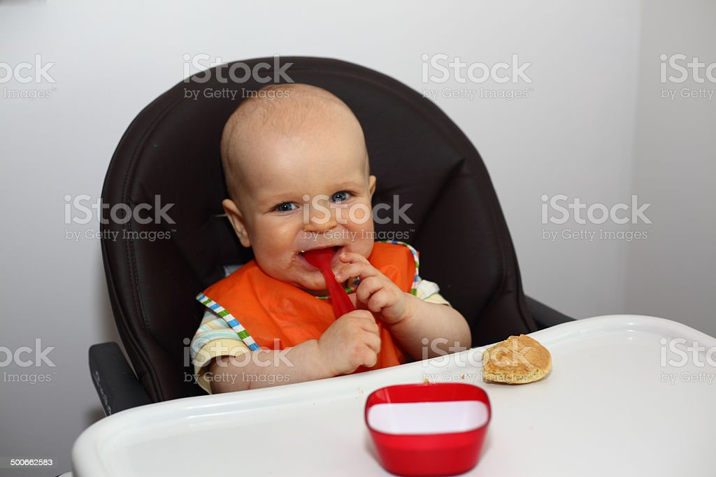 Baby boy eating with a spoon in his mouth stock photo