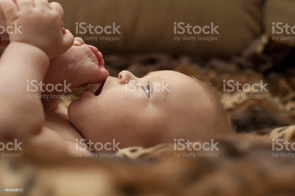 Baby boy face sucking feet mouth royalty-free stock photo