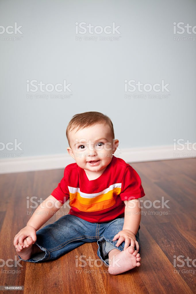 Color photo of a happy six-month-old baby boy sitting on wood floor...