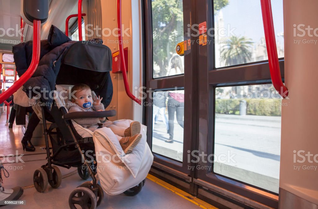 Baby boy having fun during a ride at streetcar, Spain stock photo