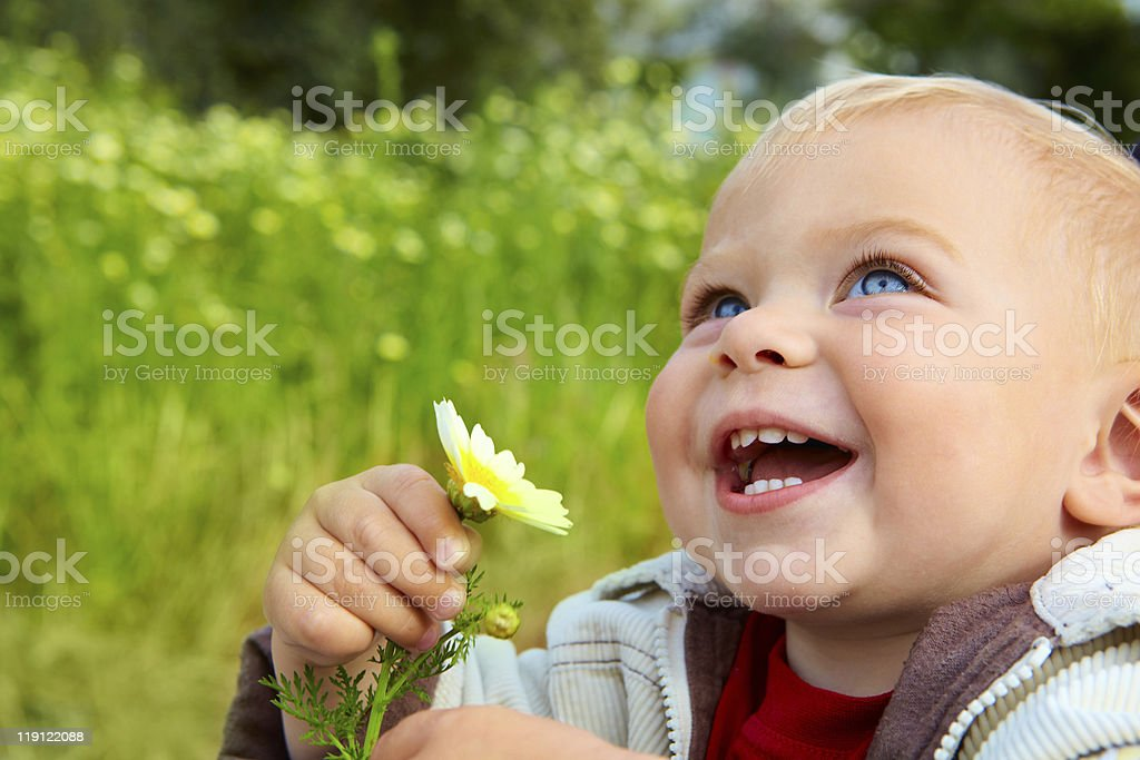 A baby boy holding a flower and smiling with meadow backdrop royalty-free stock photo
