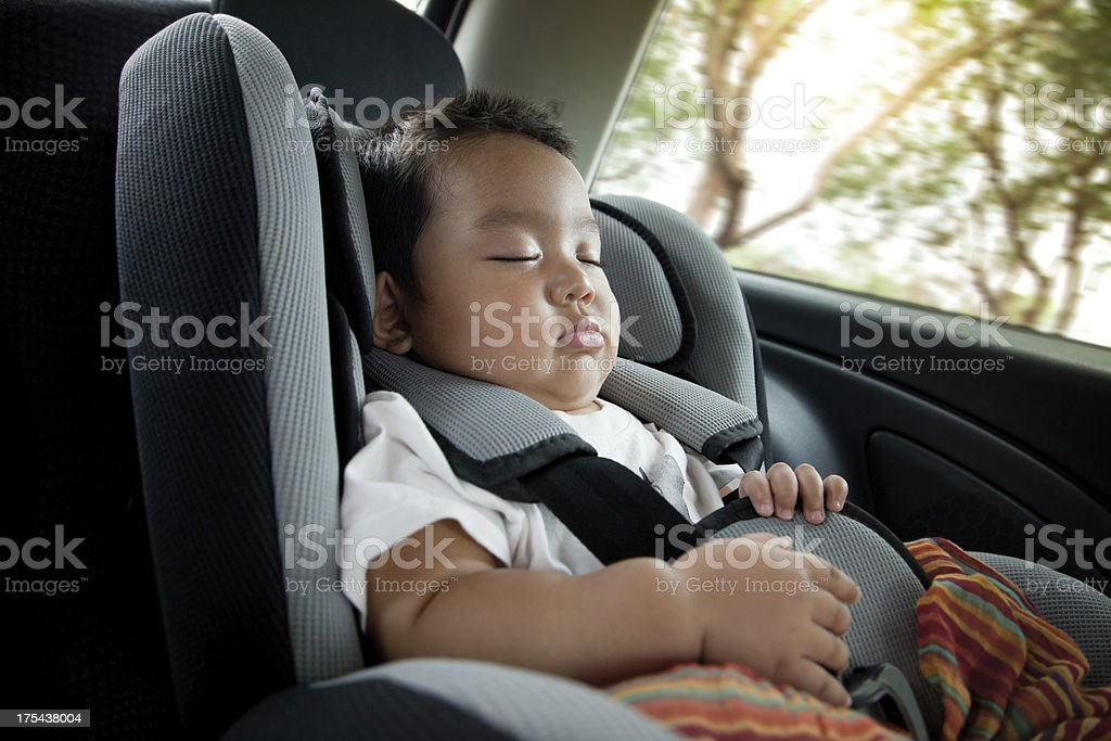 A baby boy in deep sleep in a car seat stock photo
