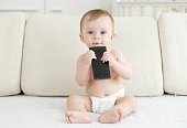 Baby boy in diapers sitting on bed and holding smartphone