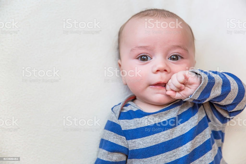 Baby Boy in Gray & Blue Laying on Fleece Blanket stock photo