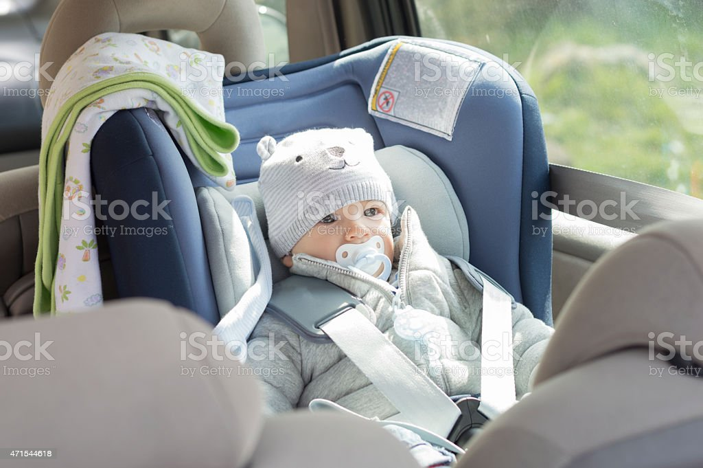 Baby boy in his child safety car seat stock photo