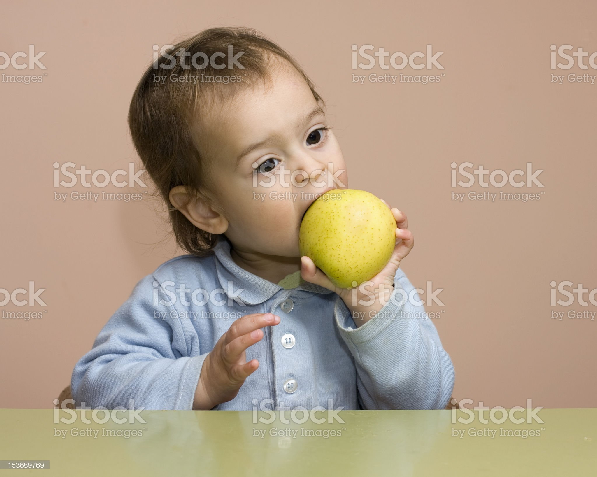 baby boy is eating yellow apple royalty-free stock photo