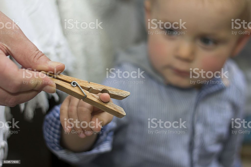 Baby boy is playing with clothespin stock photo