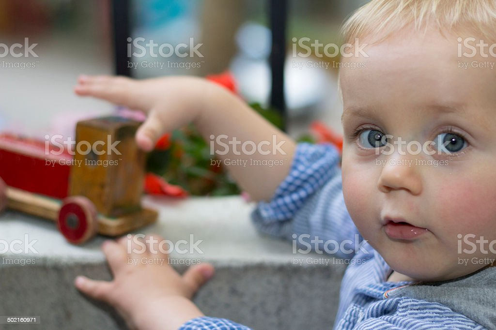 Baby boy is playing with wooden locomotive stock photo
