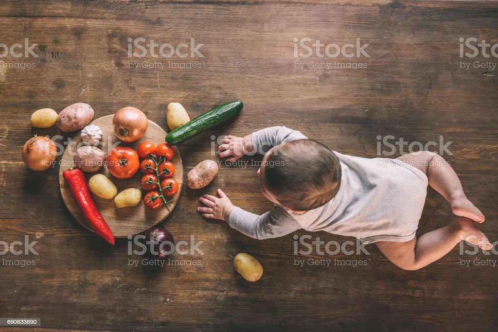 baby boy lying on kitchen table near group of vegetables on chopping board stock photo