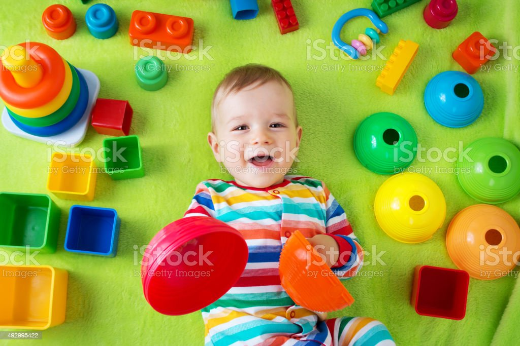Baby boy lying on the blanket with many toys around stock photo