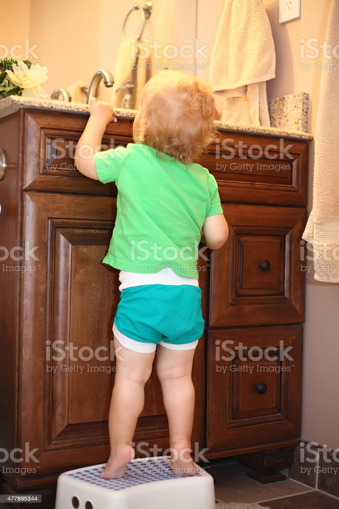 Baby boy on a step stool near the bathroom vanity stock photo