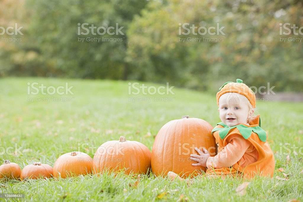 Baby boy outdoors in pumpkin costume with real pumpkins stock photo