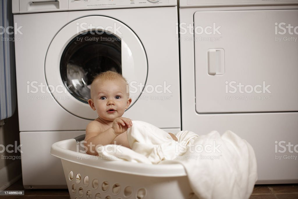 Baby boy playing in laundry basket royalty-free stock photo