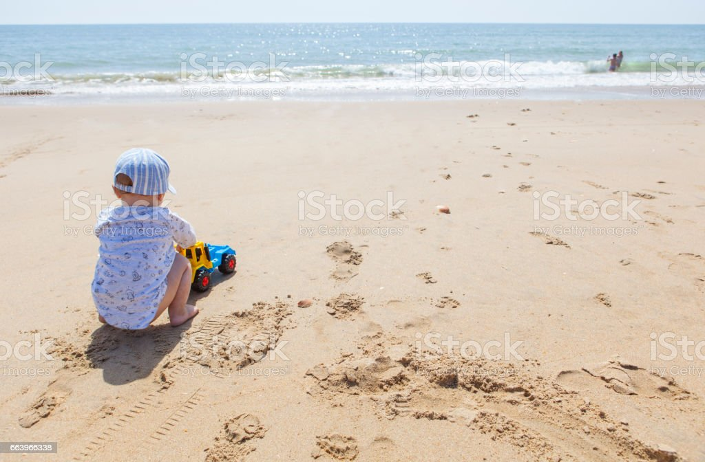 Baby boy playing on the sand while other children splash beside beach shore stock photo