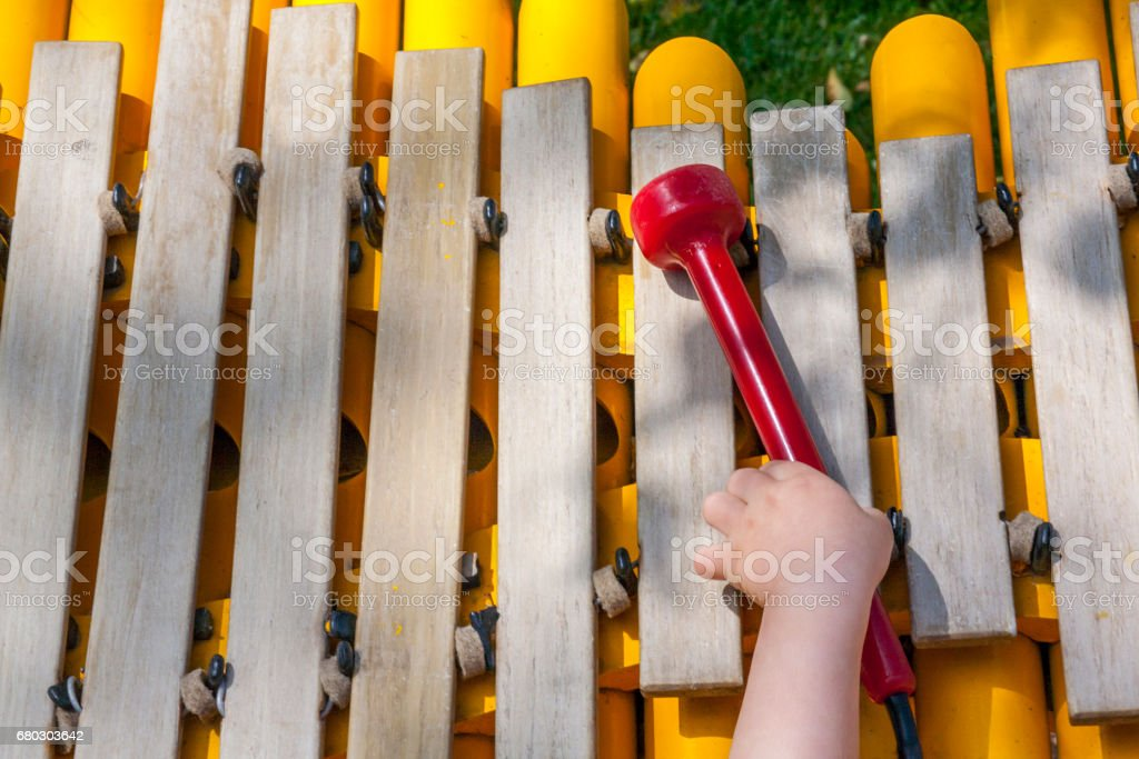 Baby boy playing take the mallet of wooden xylophone stock photo