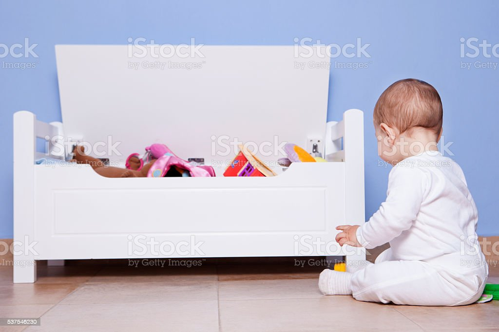 Baby boy playing with his toy trunk stock photo