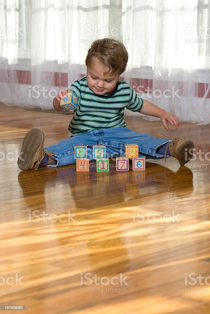 Baby Boy Playing With Number Blocks On The Floor stock photo