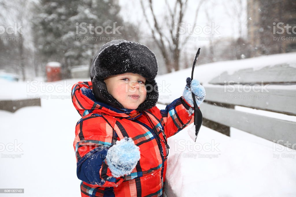 Baby boy playing with snow outdoors stock photo