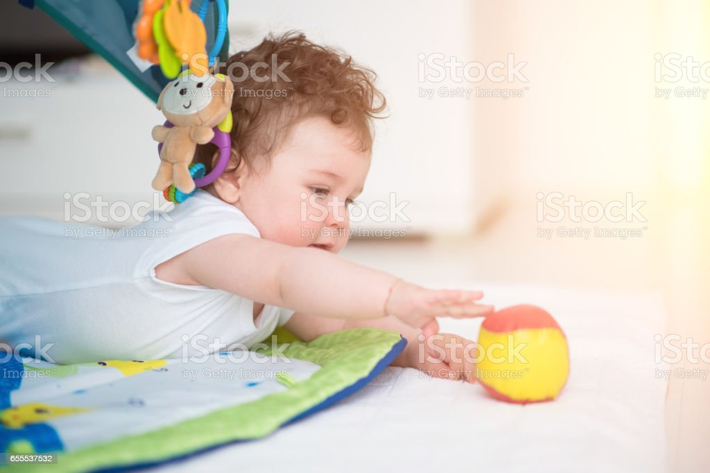Baby Boy playing with toys in playroom stock photo