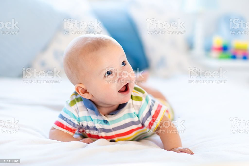 Baby boy relaxing in bed stock photo