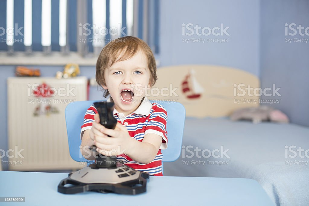 Baby boy screaming when playing computer games royalty-free stock photo