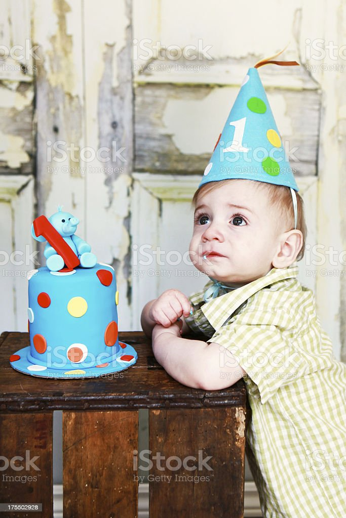Baby boy sitting at wooden crate with first birthday cake stock photo