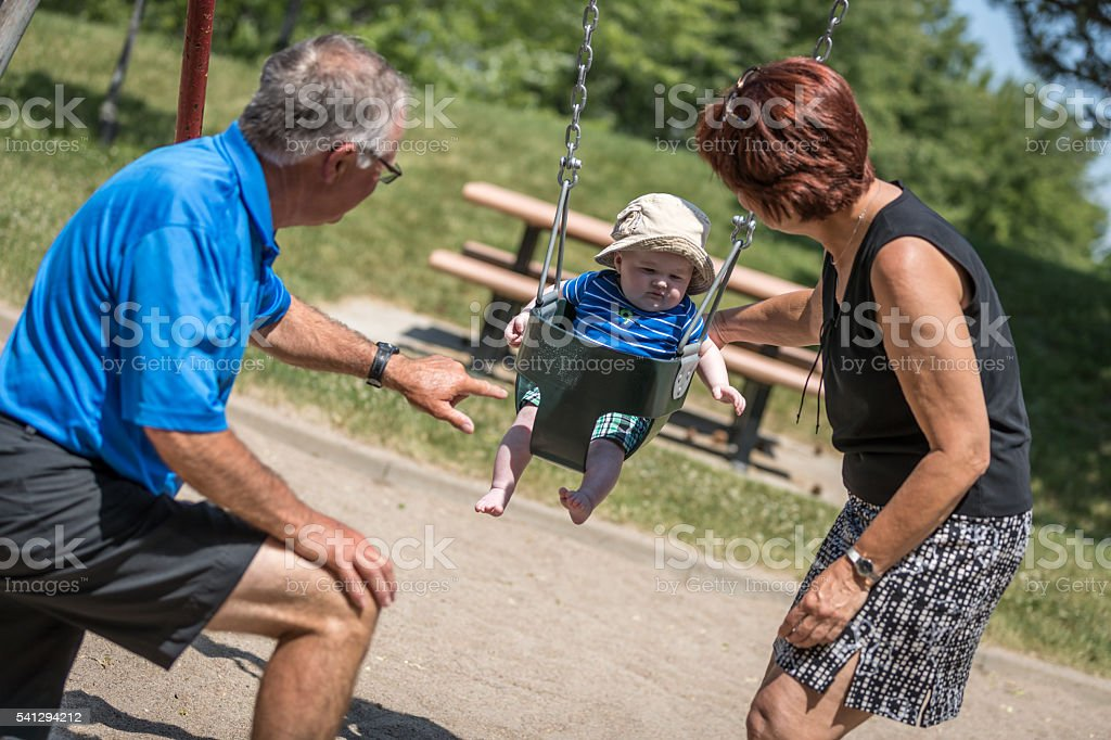 Baby Boy Sitting in Playground Swing Outdoors With Grandparents stock photo