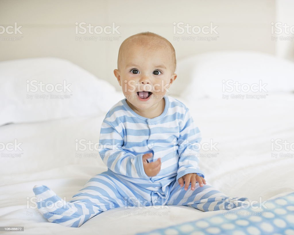 Baby boy (6-11months) sitting on bed with mouth open royalty-free stock photo