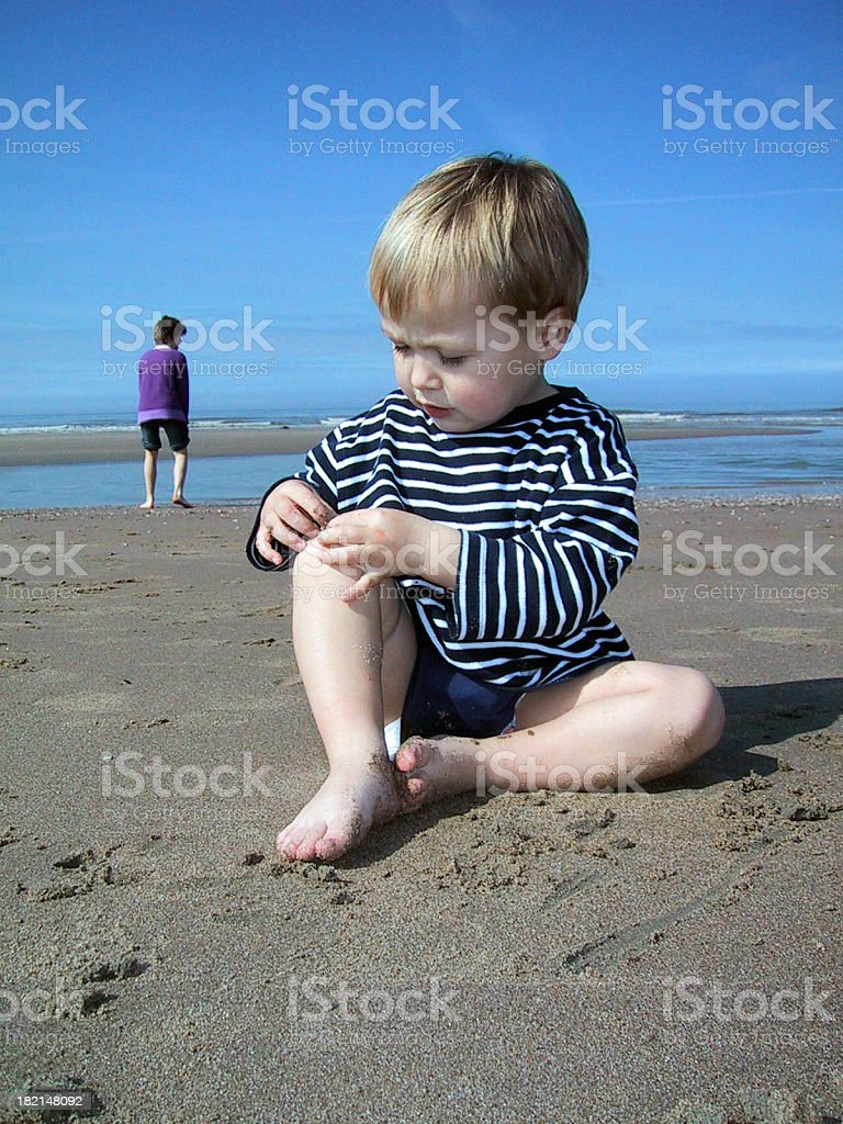 Baby boy sitting  on the beach with blue sky royalty-free stock photo