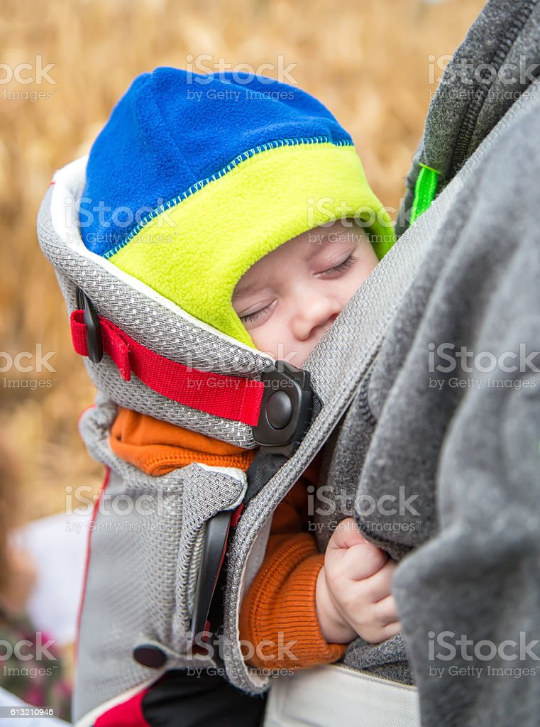 Baby Boy Sleeping in Baby Carrier stock photo