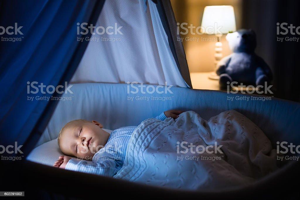 Baby boy sleeping in blue crib at night stock photo