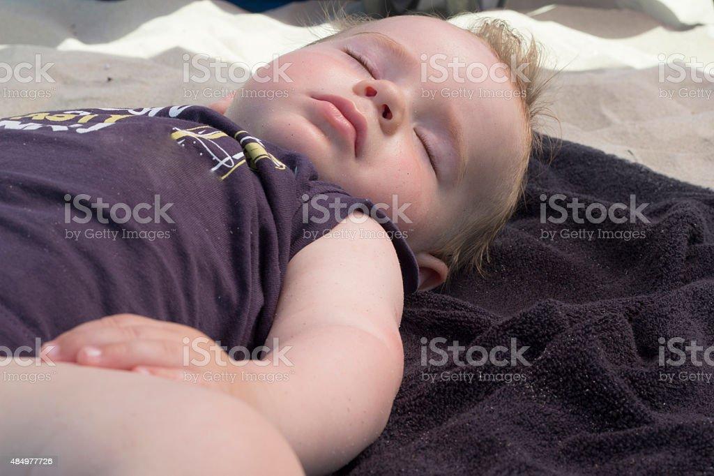 Baby boy sleeping on the beach stock photo