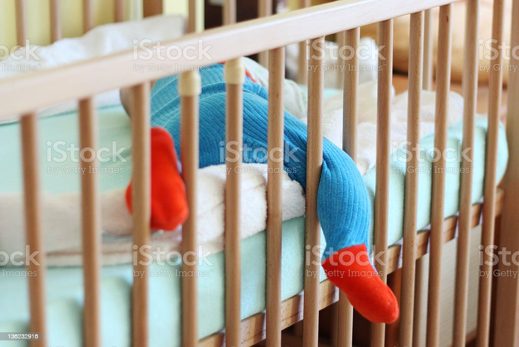 A baby boy sleeping with his leg sticking out from the crib stock photo