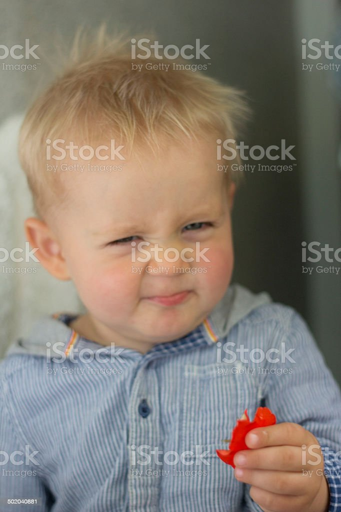 Baby boy smelling red flower stock photo