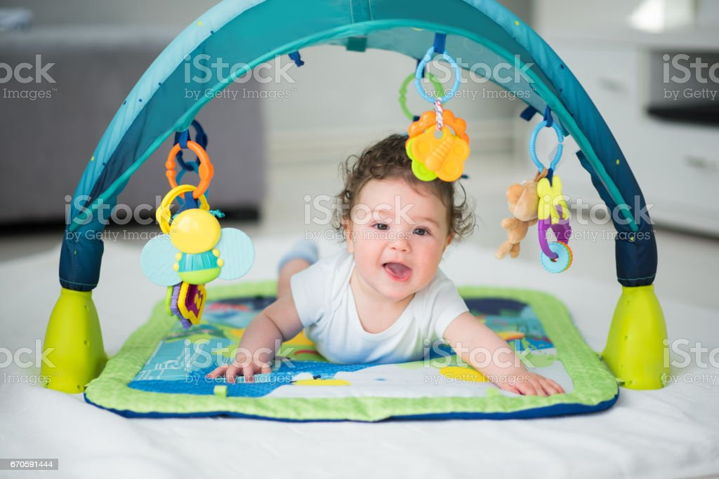 Baby Boy, smiling and playing with toys inside playpen stock photo