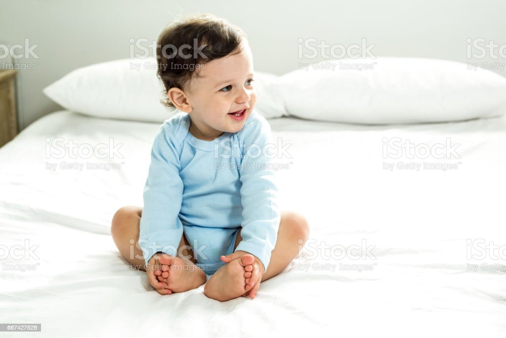 Baby boy smiling while sitting on bed at home royalty-free stock photo