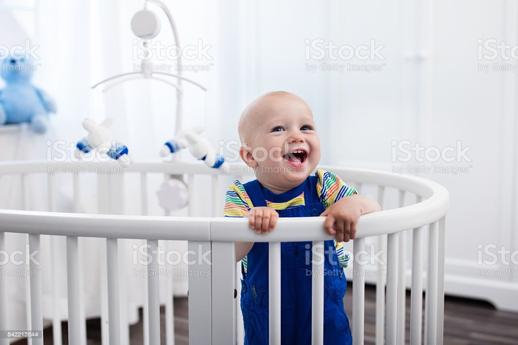 Baby boy standing in bed stock photo
