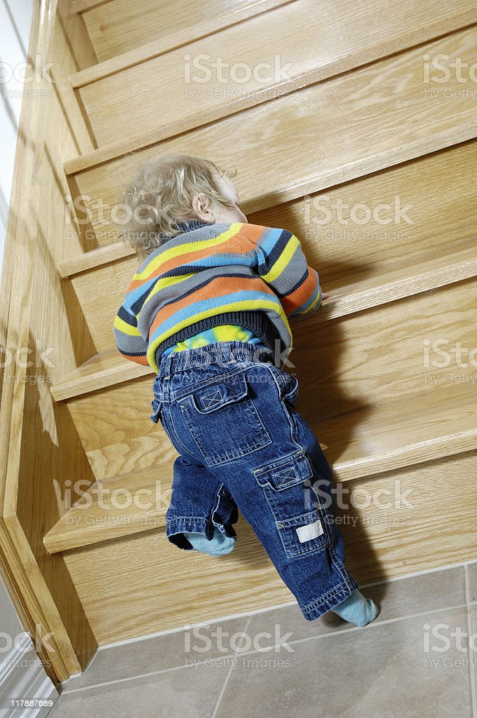 Baby boy trying to climb the stairs royalty-free stock photo