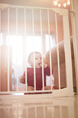Baby boy waits patiently behind baby safety gate