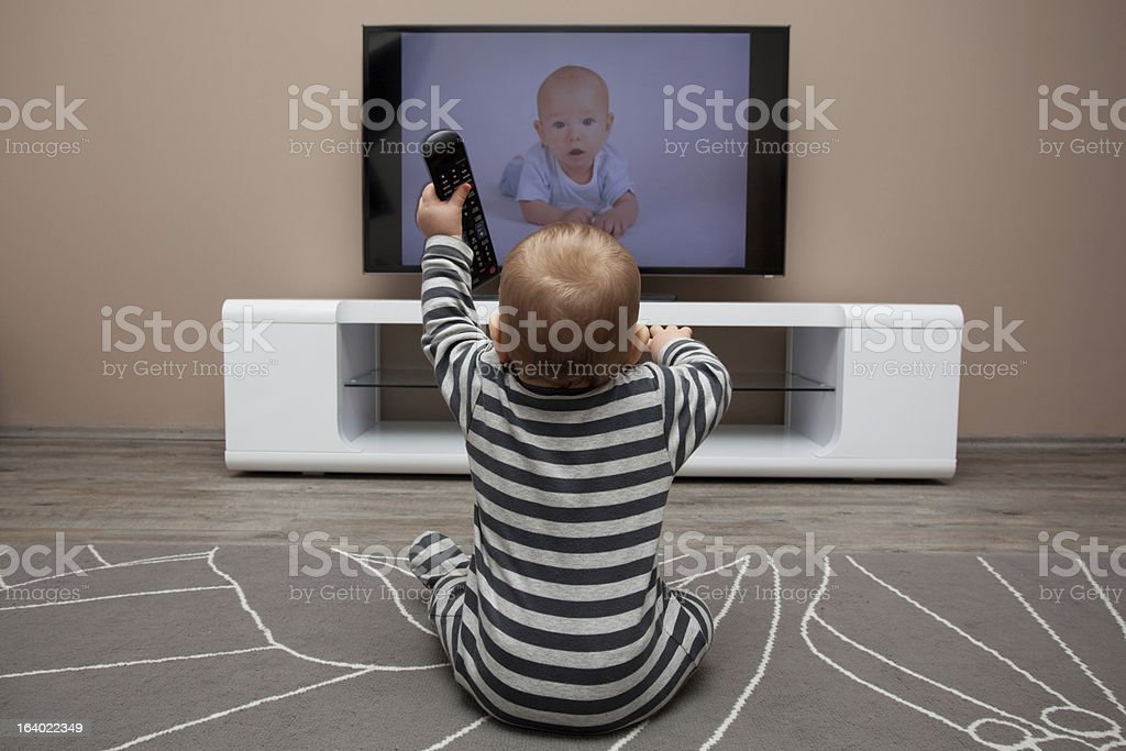 baby boy watching television stock photo