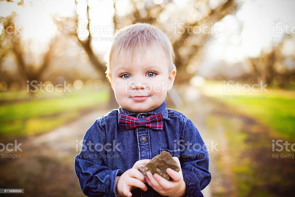 Baby Boy With a Bowtie Holding a Rock stock photo