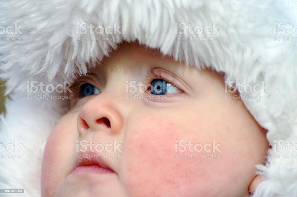 Baby boy with blue eyes and white hat stock photo